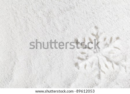 Snowflake shape imprint on snow background with copy space - stock photo