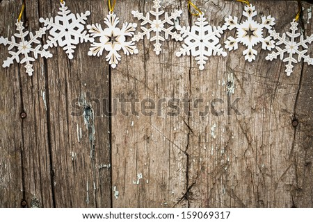 Snowflakes border on grunge wooden background. Winter holidays concept