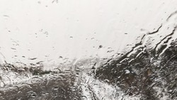 Snowflakes falling on a car window. Raining in the window.Winter and Christmas holidays.