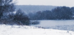 Snowflakes on a blurred background of the river and trees