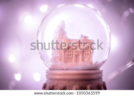 Snowglobe with purple fairy lights background