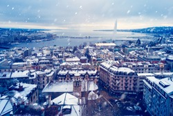 Snowing in Geneva during Winter before Christmas - Photo taken from the top of the cathedral with a view of the famous harbor of Geneva as the first snow falls on the city.