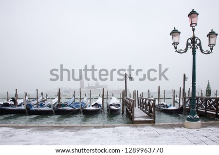 Snowing in Venice with traditional Venice gondolas on St. Mark square #1289963770