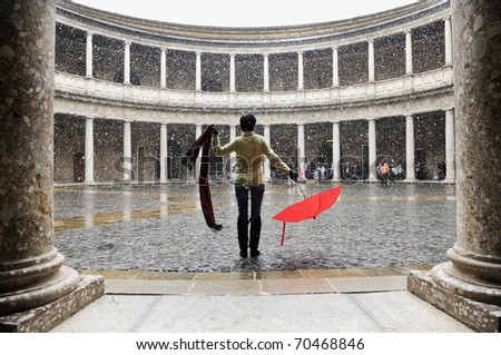 Snowing over woman with red umbrella in palace