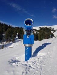 Snowmaking machine - snow cannon  on a slope in ski resort.
