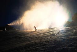 Snowmaking on slope. Skier near a snow cannon making fresch powder snow. Mountain ski resort and winter calm mountain landscape.  Winter specific