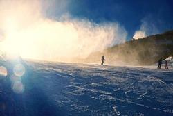Snowmaking on slope. Skier near a snow cannon making fresch powder snow. Mountain ski resort and winter calm mountain landscape.