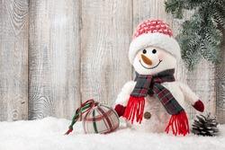 Snowman and christmas ball on snow