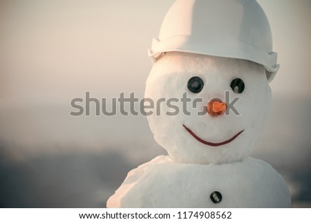Snowman builder in helmet. Happy holiday and celebration. Christmas or xmas decoration. New year snowman from snow in winter. Building and repair work. #1174908562