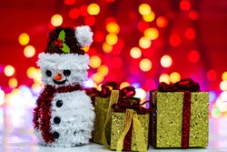Snowman Christmas figurine near glittery gifts isolated on blurred background of lights. Christmas decorations isolated