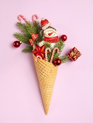 Snowman, Christmas tree twigs and lollipop in a waffle cone. Pink background. Christmas card. An original sweet gift.