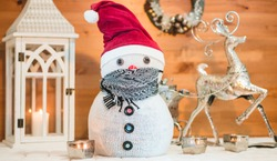 Snowman in a red cap and protect mask with wooden background. Christmas decoration