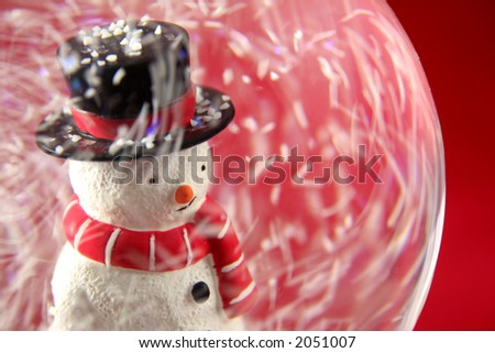 Snowman in snowglobe in swirl of snow with red background