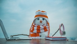 Snowman in winter with laptop, headset and book. Xmas or christmas decoration, audio book. New year snowman in hat. Happy holiday celebration, new technology. Christmas and education, fairytale.