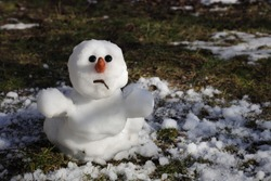 Snowman is melting in the sun. Thaw, warm winter, early spring, global warming, climate change background.