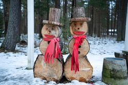 Snowman made from logs. Reusable snowmen. Snowmans with hats and scarves. Snow is meling, but snowman is going on for ever. Wooden decorations for christmas holidays. Happy looking logs