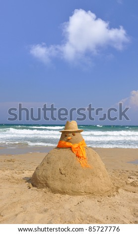 Snowman made of Beach Sand Wearing Straw Hat and Orange Scarf on Sunny Blue Sky Day