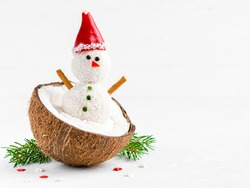 Snowman made of coconut balls in coconut shell. Healthy christmas dessert. Funny and cute new year sweets. Festive food. Winter and christmas concept. Greeting card design.White background. Copy space