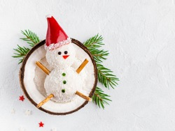 Snowman made of coconut balls lying in coconut shell. Funny and cute christmas and new year food (dessert). Fir branches, top view, copy space. Winter and christmas concept. Flat layout template.