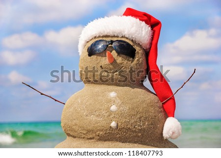 Snowman made out of sand against the sky. Holiday concept can be used for New Year and Christmas Cards