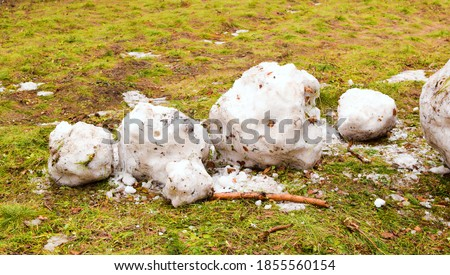 Snowman melted with the arrival of spring on a background of green grass. Destroyed, dirty snowman lies on the ground. Holiday of Christmas and New Year is over. Remains of a snowman.