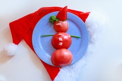 Snowman of tomatoes, peppers, ham and herbs on a plate. Christmas decor from food. Isolated on a white background. Copy space. Santa hat
