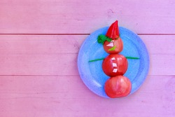 Snowman of tomatoes, peppers, ham and herbs on a plate. Christmas decor from food. Isolated on a pink background. Copy space