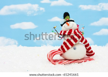 Snowman on a candy cane sleigh on a blue sky background, snowman having fun