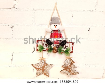 Snowman, toys, inscription and Christmas holiday decorations. The decorations are attached to the wall in white and serve as decoration in the interior of the house.