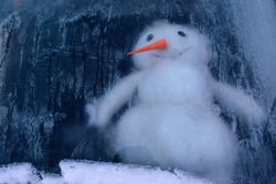 Snowman under the ice or behind the glass. Icy patterns from frost, snow. Big red nose. New Year, Christmas holiday concept.