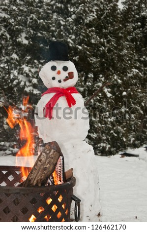 Snowman warming up by the campfire.