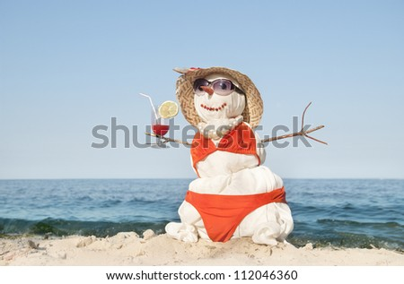 Snowman with cocktail at the beach