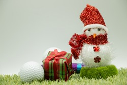 Snowman with golf ball and present on green grass background. Merry Christmas for golfer.
