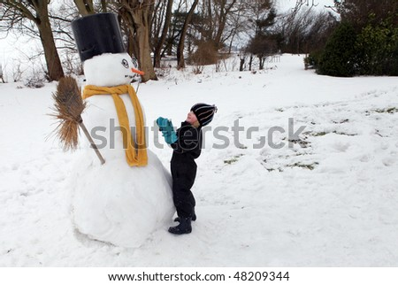 snowman with scarf and carrot nose in winter