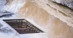 Snowmelt into Storm Drain. Heavy rain melts snow and pours into a storm drain after a snowfall.