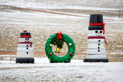 Snowmen and a wreath made out of recycled tires for Christmas decorations, horizontal