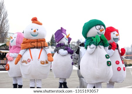 snowmen dance on a festive area near the carousel where they spend the winter holidays, the theme of holidays and entertainment  #1315193057