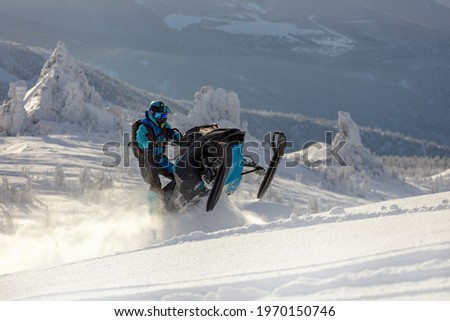 snowmobile. a guy rides a snow bike in the mountains against the backdrop of a ridge of rocks and a snow-covered valley. prof snowmobiler stands on a track with snow swirls. Stock photo ©