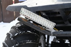 snowmobile headlight in the shape of a rectangle against the background of huge wheels