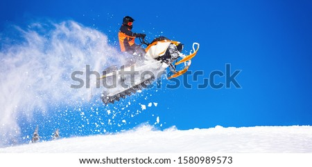 snowmobile jump straight up. the guy is flying and jumping on a snowmobile on a background of blue sky leaving a trail of splashes of white snow. bright snowmobile and suit. No brands. copy text Stock photo ©