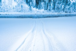 Snowmobile tracks in deep snow. Twisting traces of a snowmobile crossing snow covered field