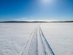 Snowmobile tracks leading off towards the horizon, across a frozen lake in the northernmost parts of Sweden, Lapland. Deep blue sky with almost no clouds, sun just outside the image.
