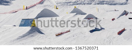Snowpark with ski ramps, kickers, rails for big air jumping, jibbing, etc. for freestyle snowboarders and skiers #1367520371
