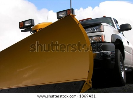 Snowplow and truck against clouds.