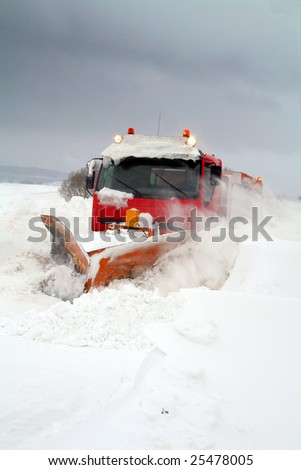 snowplow clear snow of road during winter blizzard or storm