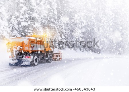 Snowplow cleared the snow-covered icy road - Shutterstock ID 460543843