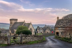 Snowshill church in the Cotswolds gloucestershire with lane leading past a cottage towards red telephone box and country pub