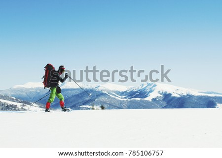 Snowshoe walker running in powder snow with beautiful sunrise light. Outdoor winter activity and healthy lifestyle #785106757