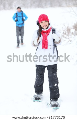 snowshoeing winter hiking. Active couple on snowshoes outdoors in snow walking in natural park in Canada, Quebec.