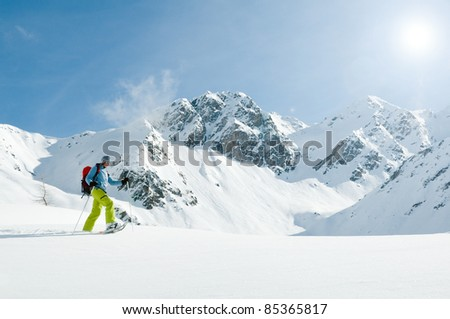 Snowshoeing - woman trekking in winter mountains (copy space)